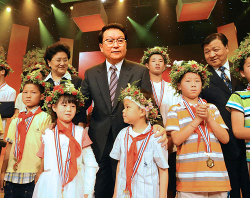 Li Changchun, member of the Political Bureau Standing Committee of the Communist Party of China (CPC) Central Committee, center, poses for a photo with little heros in quake rescue on Friday, June 27, 2008. [Photo: Xinhua]