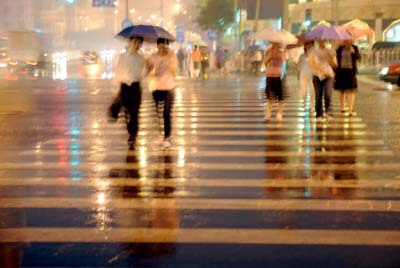 The picture taken on June 27 shows people walk on a crossroad in Beijing's Xuanwu District in the rain. The rainfall so far this year in Beijing was the highest in 10 years, the municipal meteorological bureau said.