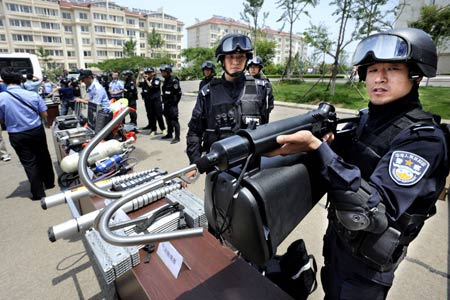A policeman introduces the function of a kind of new equipment to be used during the Beijing Olympic Games, in Qingdao, a co-host of the Games in east China's Shandong Province, on June 27, 2008. An anti-terror drill was held Friday here, as the city will hold sailing competition of the 2008 Olympic Games from August 8 to 24.