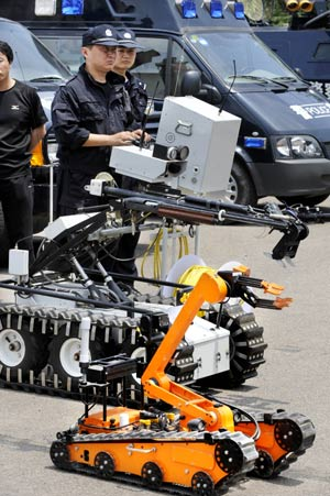 Policemen operate the anti-explosive robots during a drill in Qingdao, a co-host of the Games in east China's Shandong Province, on June 27, 2008. An anti-terror drill was held Friday here, as the city will hold sailing competition of the 2008 Olympic Games from August 8 to 24.