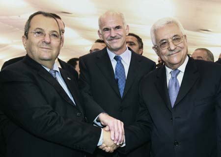 Palestinian President Mahmoud Abbas (R), President of the Socialist International George Papandreou (C) and Israel's Defence Minister Ehud Barak (L) shake hands during a Socialist International congress in Lagonisi July 1, 2008. The three-day congress discusses climate change, peace and the resolution of conflicts, the world economy and migration.