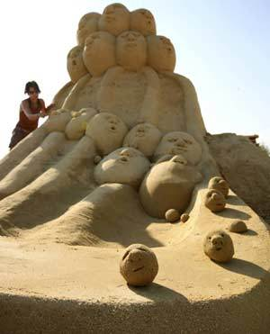 An artist makes final touches on a sand sculpture before the official opening of the First international sand sculptures festival in the Black Sea costal town of Bourgas, some 390 km (246 miles) east from capital Sofia, June 30, 2008.