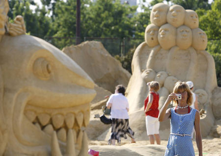 A tourist takes pictures of a sand sculpture before the official opening of the First international sand sculptures festival in the Black Sea costal town of Bourgas, some 390 km (246 miles) east from capital Sofia, June 30, 2008.