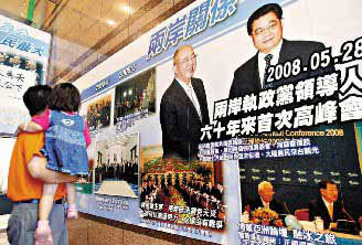 A man, carrying his kid in arms, watches the photo of Hu Jintao meeting with KMT chairman Wu Poh-hsiung in May at the KMT headquarters building in Taipei. [Photo: United Evening News]