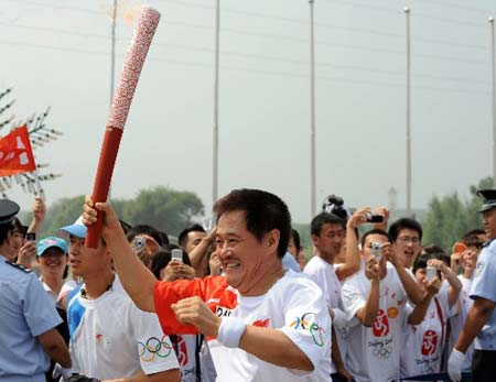 Torchbearer Zhao Benshan, a famous comedian runs during the 2008 Beijing Olympic Games torch relay in Shenyang, capital of northeast China's Liaoning Province, on July 17, 2008.