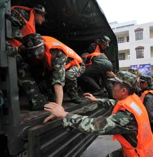 Soldiers and military officers get on a truck to reach the areas vulnerable to typhoon attacks in Fuzhou, capital of east China's Fujian Province, July 18, 2008.