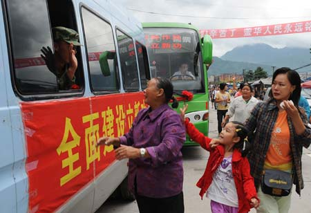 Local villagers say goodbye to the People's Liberation Army (PLA) soldiers in the quake-hit Yinghua Town in Shifang City of southwest China's Sichuan Province, July 21, 2008. Some 1,700 PLA paratroopers left the Yinghua Town after completing their quake relief operations.