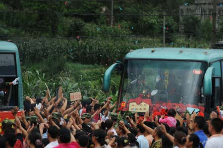 Local villagers express their thanks to the People's Liberation Army (PLA) soldiers as they are leaving the quake-hit Yinghua Town in Shifang City of southwest China's Sichuan Province, July 21, 2008.