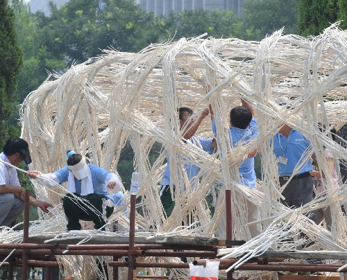 Workers are busy with erecting the structure for a Bird's Nest-shaped flower sculpture at Beijing's Tian'anmen Square on Tuesday, July 22, 2008.