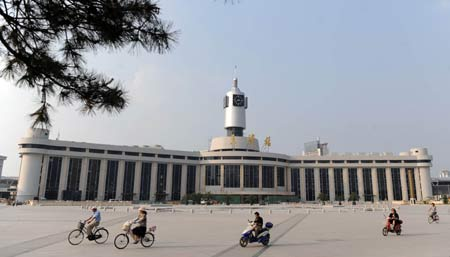 People ride past the square in front of the Tianjin Railway Station in north China's Tianjin Municipality, July 21, 2008.