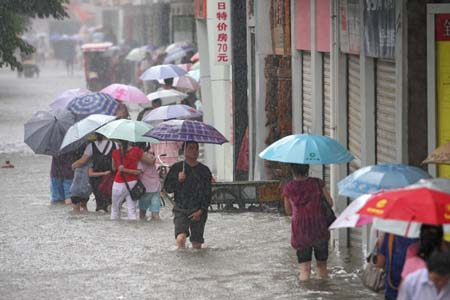 Pedestrians wade on a flooded road in Xiangfan City, central China's Hubei Province, July 22, 2008. A heavy rain hit the city Tuesday causing some roads flooded. The local PLA soldiers and officers have thrown themselves into the fight against the floods. (Xinhua/Yu Xiang)