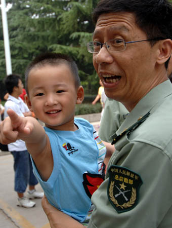 "Lang Zheng (L), known as the ""Salute Boy"", poses for a picture in the arms of an officer of Tangdu Hospital while leaving the hospital after two months of treatment, in Xi"