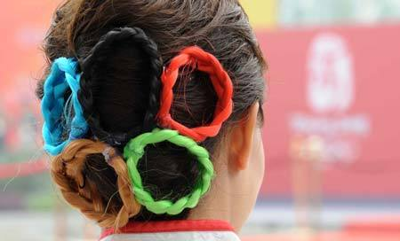 A volunteer wear a five-ring hair spin at Olympic Village in Beijing.