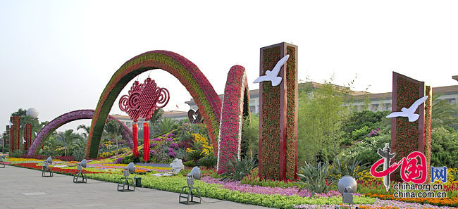 In the western corner of Tian'anmen Square, the flower terrace themed 'A Harmonious Society Brought about by the Reform and Opening-up' is decorated by the rainbow gates and the Chinese knots and a colorful brook flowing down from the flower mountain. The brook has the pattern of 56 flowers and joined hands symbolizing the unity of 56 nationalities of China.