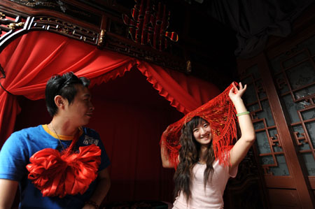 A couple demonstrate Chinese traditional wedding custom in the guest room of the Olympic homestay dwelling at No. 39 of the South Guanfang Hutong in Beijing, China, July 29, 2008.