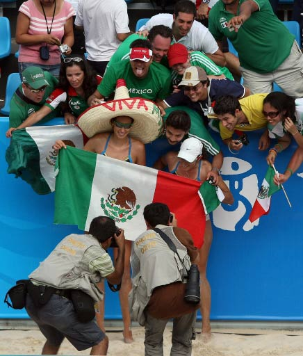 Mexico's Bibiana Candelas with teammate Mayra Garcia (C) pose with supporters after winning against Greece in their women's preliminary beach volleyball match at the 2008 Beijing Olympic Games on August 12, 2008.[AFP]