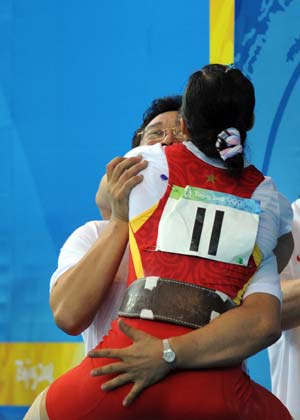 Chen Xiexia of China hugs her coach after winning the first gold for the Chinese Delegation with 95 kilos in the snatch and 117 in the clean and jerk for a total of 212 kilos at the Beijing 2008 Olympic Games in the women's 48kg weightlifting in Beijing, China, Aug. 9, 2008. Chen broke the Olympic record in this event. (Xinhua/Yang Lei)