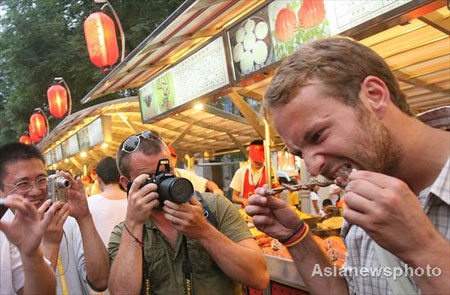 People take photos as a foreign tourist eats a snack at the Donghuamen food street in downtown Beijing, August 13, 2008. Centipedes, sharks, scorpions, crickets are all served as delicious food at the night fair on Donghuamen food street.
