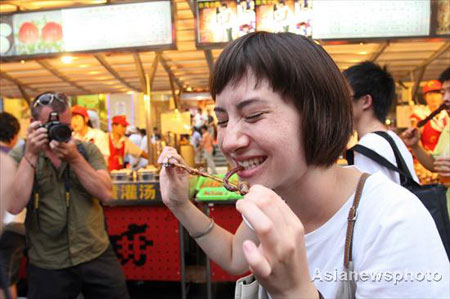 A foreign tourist eats a snack at the Donghuamen food street in Beijing, August 13, 2008. [Asianewsphoto]