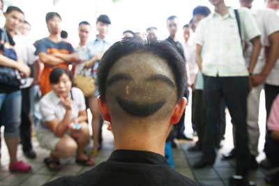 Zheng Yu, 30, who sells his laughs in a Chongqing street, shows his hairstyle on August 3, 2008.