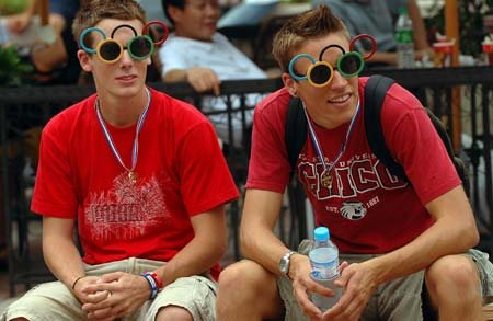 Two foreign tourists wearing sunglasses shaped into the logo of the Olympic Games rest at Wangfujing Street in Beijing on August 13, 2008. More and more foreign tourists visit Beijing as the Beijing Olympics are going on here.