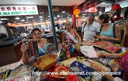 Foreigners select silk handicrafts at a store in Xiushui Market (Silk Street market), a popular tourist market, in Beijing on August 13, 2008.