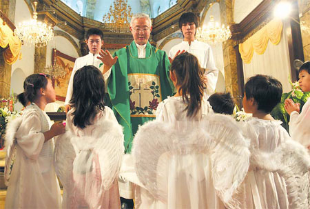 Father Peter Zhao Jianmin (center) conducts mass at the Catholic Church of Xuanwumen in Beijing, August 17, 2008. [China Daily]