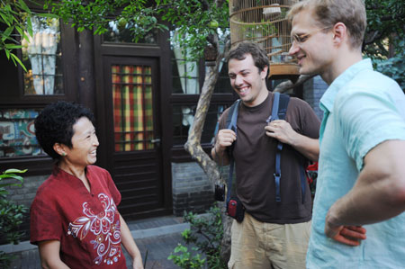 Wang Zhixi, hostess of an Olympic homestay for foreign visitors, talks to two American guests about the traditional Chinese architecture in Beijing August 15, 2008. Wang's home, at Dajinsi Hutong near Shichahai Lake, a tourist attraction in downtown Beijing, is one of about 600 homestay families chosen for foreign visitors during the Beijing Olympic Games. [Xinhua]