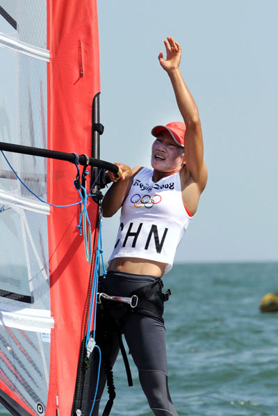 Chinese Yin Jian reacts after winning China's first ever Olympic sailing gold. Yin was crowned champion of RS:X Women at the Olympic Sailing Regatta here on Wednesday. [Song Zhenping/Xinhua]