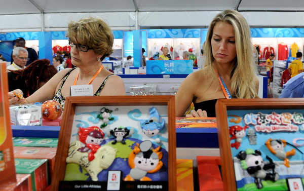 Foreign tourists buy Olympic souvenirs in the commercial and cultural street of the Beijing Olympic Village on August 20, 2008.