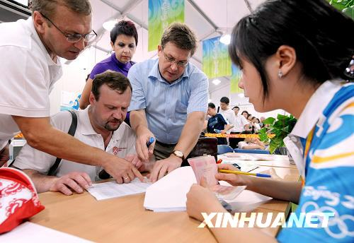 Russian visitors fill out forms before entering the Olympic Village on Friday, August 22, 2008. [Photo: Xinhuanet]