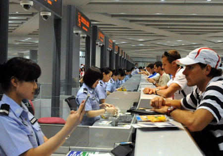 Passengers check in in front of counters at the Beijing Capital International Airport in Beijing, capital of China, Aug. 25, 2008. The airport saw a peak traffic volume on Monday as many Olympic delegations left the Chinese capital. A total of 32,596 passengers would leave Beijing throughout the day, doubling the usual figure. (Xinhua/Tang Zhaoming)