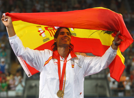 Rafael Nadal of Spain holds the national flag of Spain at the awarding ceremony of the men's singles gold medal match of Beijing Olympic Games tennis event against Fernando Gonzalez of Chile in Beijing, China, Aug. 17, 2008. Nadal won the match 3-0 and claimed the title in this event.