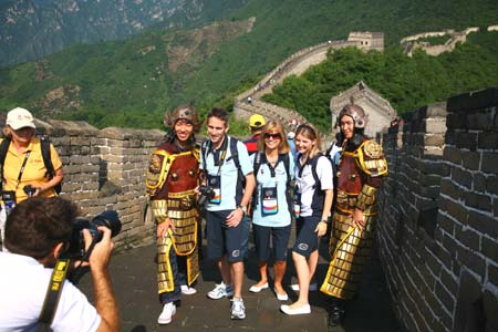 Foreign tourists pose for pictures with two tourists wearing ancient Chinese armatures the Mutianyu section of the Great Wall in Beijing, capital of China, August 18, 2008. The Great Wall attracts many foreign visitors and athletes during the Beijing 2008 Olympic Games. [Xinhua]