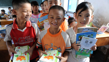 Deng Wenjun (middle) receives his textbook free of charge with his classmates studying in the Second Primary School in Zhangshu City of south China's Jiangxi Province on September 1, 2008.