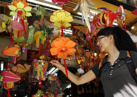 A pedestrian chooses lanterns for the Mid-Autumn Festival at a store in Hong Kong, south China, Sept. 7, 2008. The Mid-Autumn Festival, a traditional Chinese holiday for family reunion and mooncakes, falls on Sept. 14 this year. [Liu Lianfen/Xinhua]