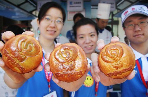 Paralympics volunteers present homemade mooncakes bearing the logo of the Beijing Olympic Volunteers Program at a volunteer service station located in downtown Beijing on Thursday, September 11, 2008. These special mooncakes are gifts for volunteers scheduled for duty during the Mid-Autumn Festival on Sunday. [Photo: Xinhua]