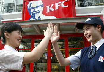Two KFC staff clap hands to cheer each other outside a KFC restaurant in Shanghai April 20. [Xinhua]