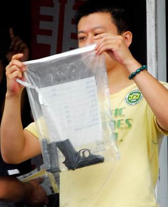 A police shows the pistol used by the suspect.