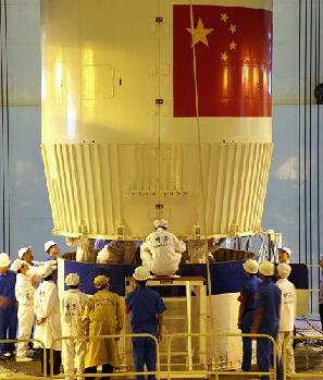 Technicians help the Shenzhou VII spacewhip dock with the Long-March II-F rocket at an assembly plant in Jiuquan, Gansu province. [Xinhua]