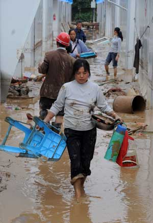 People with their belongings flee their homes after a landslide caused by torrential rain in Leigu township, Beichuan county of southwest China&#38;apos;s Sichuan Province on Sept. 24, 2008. 