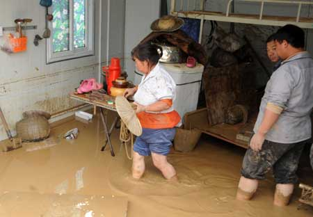People collect their belongings after a landslide caused by torrential rain in Leigu township, Beichuan county of southwest China's Sichuan Province on Sept. 24, 2008.
