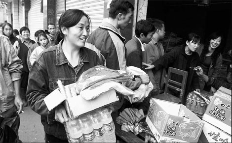 Quake victim Zhang Chunfang (left) from Mingjing village, Jiangyou, Sichuan province, receives government aid on Saturday.