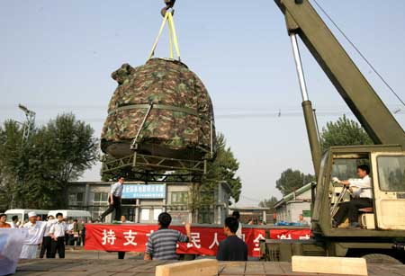 The re-entry module of China's Shenzhou VII spacecraft is lifted onto a truck at Beijing's Changping railway station Sept. 30, 2008. The module was shipped to Beijing Tuesday afternoon, two days after its safe landing in northern China's Inner Mongolia. [Zha Chunming/Xinhua]