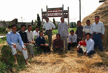 The villagers take pictures at the entrance to Xiaogang Village.