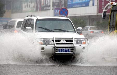 A vehicle trudges its way through the waterlogged street in Haikou, capital of south China's Hainan Province, Oct. 14, 2008. Monsoon rain hit the island in recent days flooding 12 cities and counties and causing two dead in the region. [Photo: Xinhua Photo]