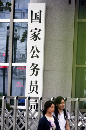 People walk past the gate of the State Administration of Civil Service in Beijing in this August 30. [China Daily]