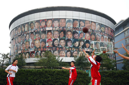 Students exercise next to a wall of smiling faces in Nanjing, Jiangsu Province October 20, 2008. The wall, 10 meters high and 40 meters long, has more than 300 pictures of smiling faces, all students of the middle school. The school hoped to create a light and harmonious environment for the students. [CFP]