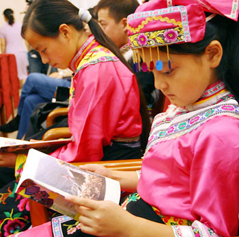  Two Qiang girl student from the quake-hit Sichuan Province reads a text book about the Qiang culture during a book donation ceremony held in Beijing on September 10, 2008.
