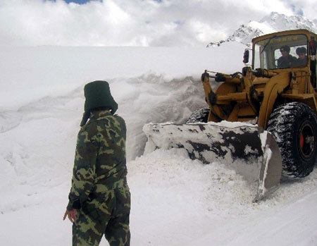 A heavy snow, which began to fall on Sunday in southwest China's Tibet, has left two people missing and blocked roads in many places. Armed police are struggling to clear roads to restore traffic.